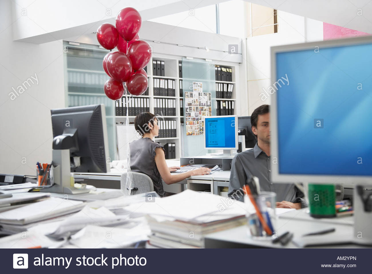 Businesswoman at desk with balloons tied to chair and coworker in foreground Stock Photo