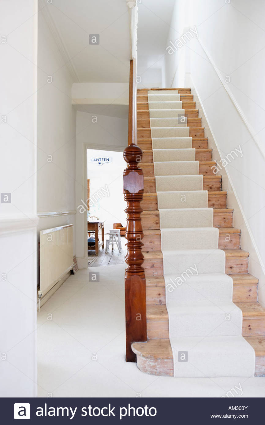 Staircase with runner and empty hallway - Stock Image