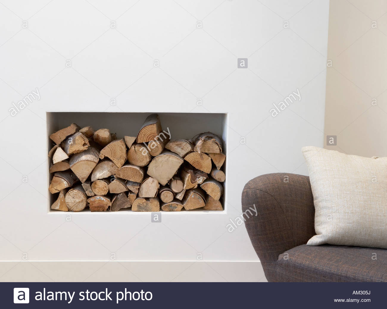 Pile of wood beside chair indoors - Stock Image