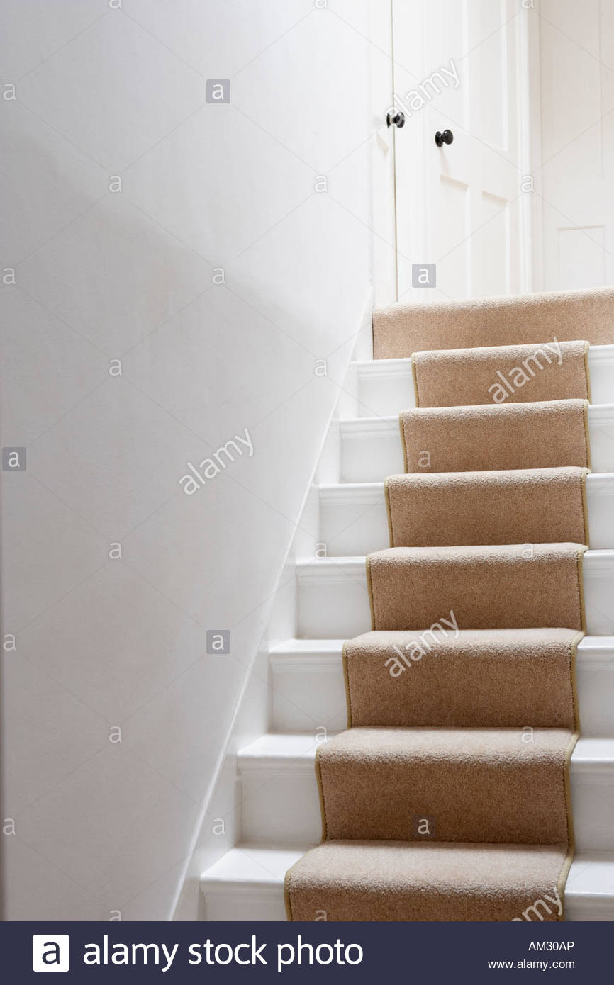 Stairs with beige runner - Stock Image
