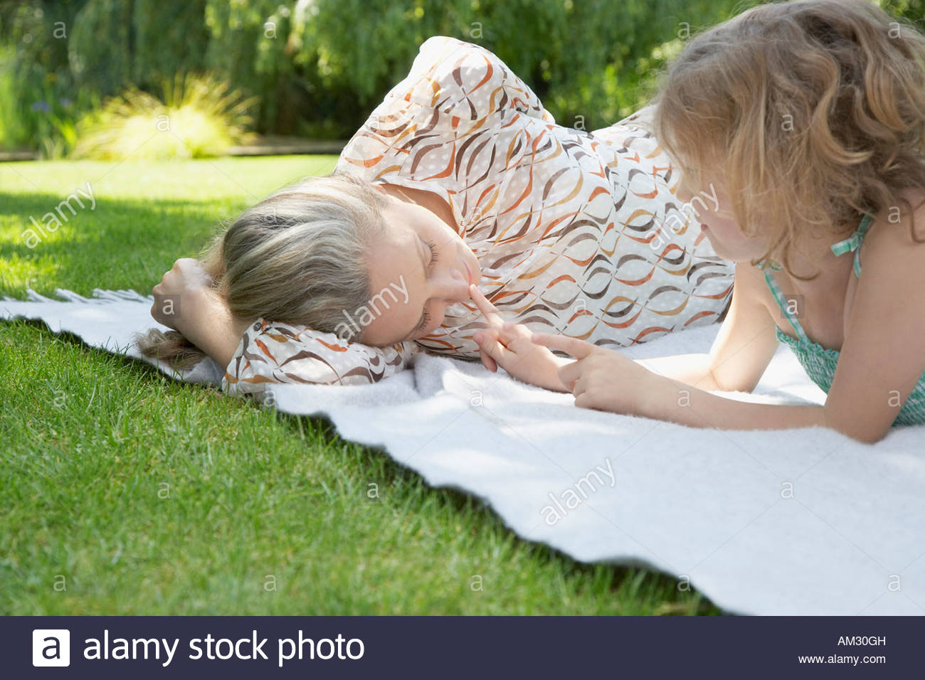 Woman and young girl lying down on blanket outdoors - Stock Image