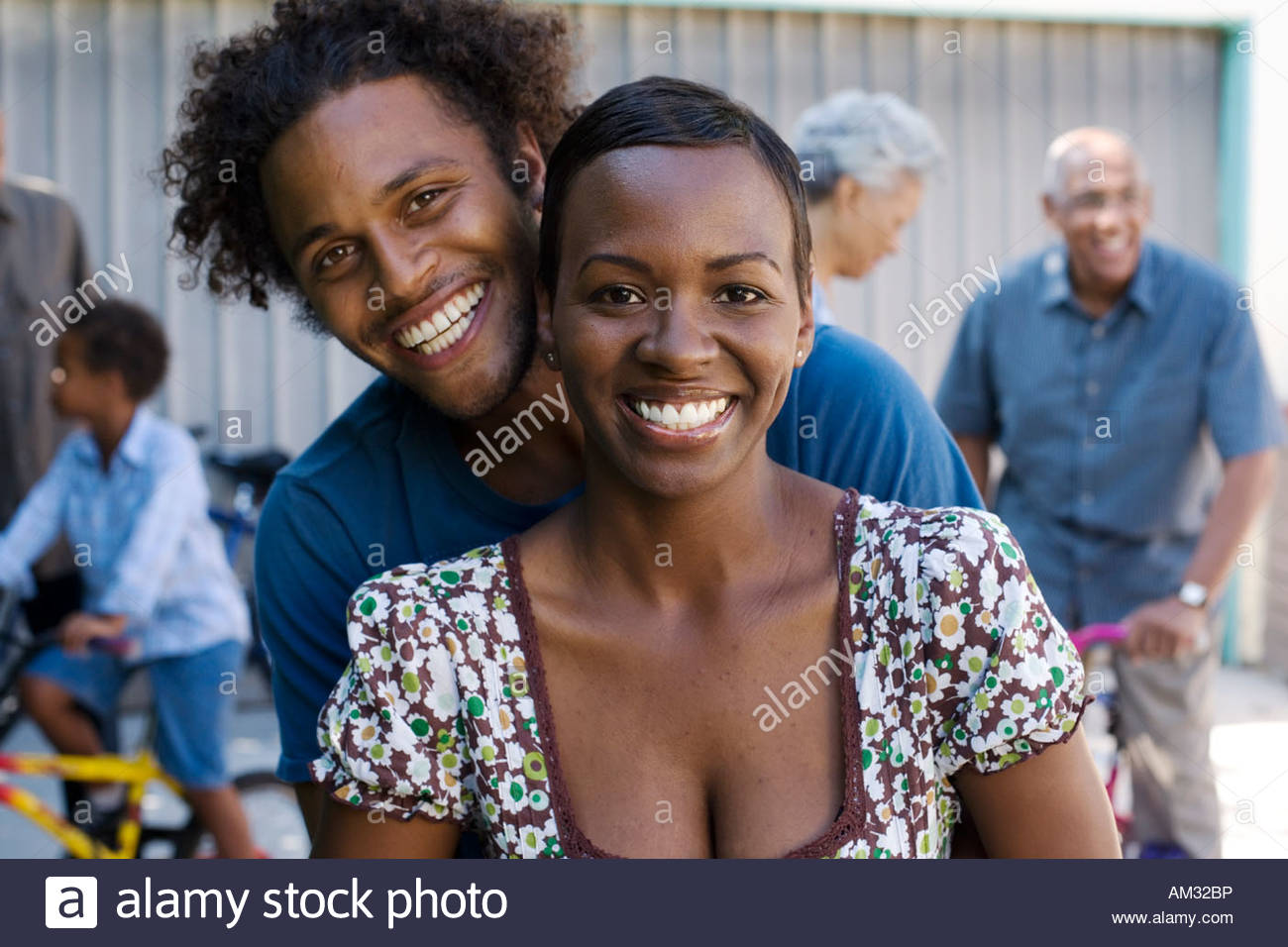 Couple embracing in driveway with people in background - Stock Image