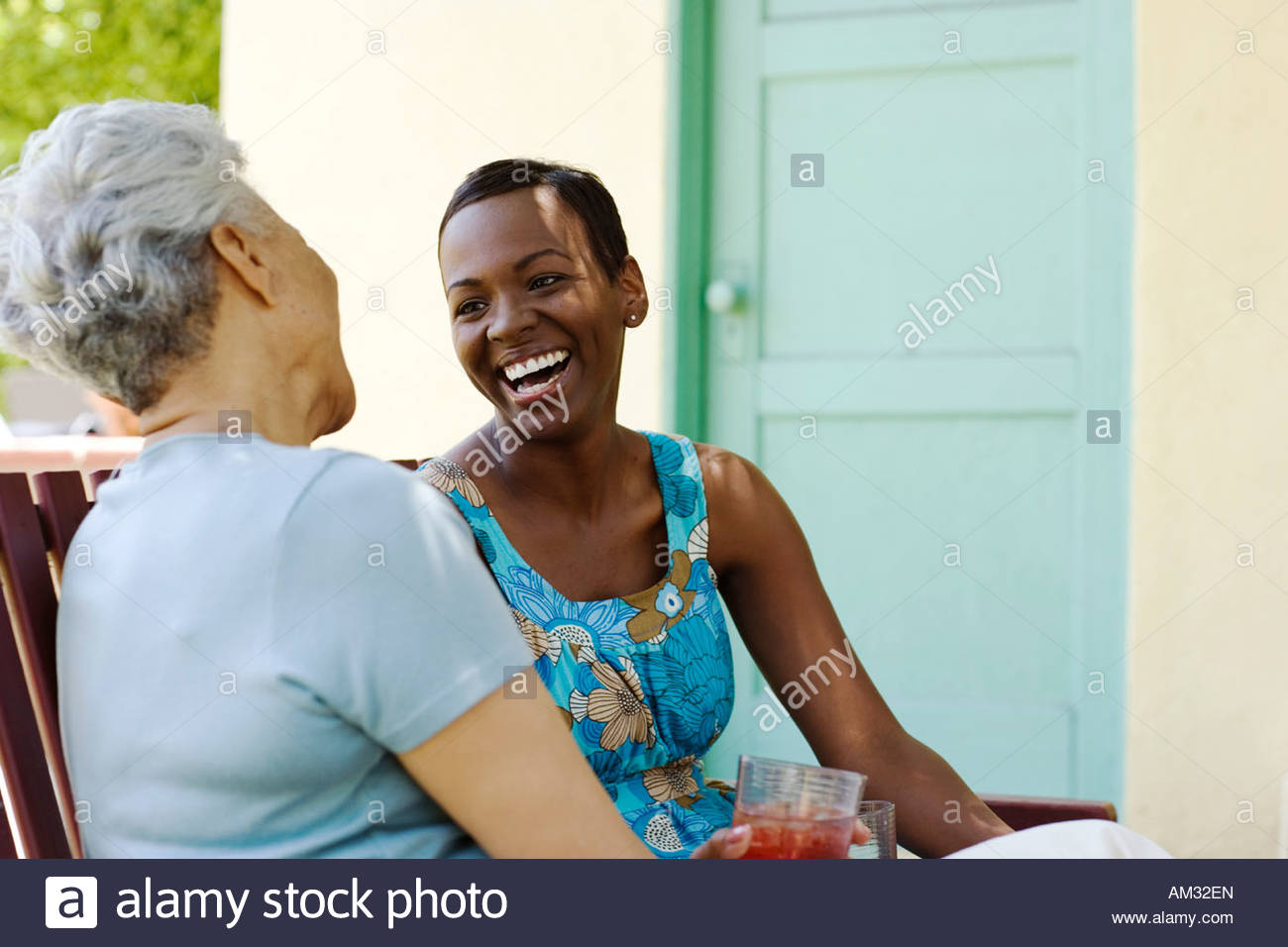 Two women sitting outdoors on wooden bench laughing Stock Photo