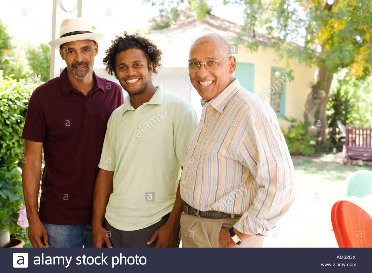 Three men outdoors on patio smiling - Stock Image