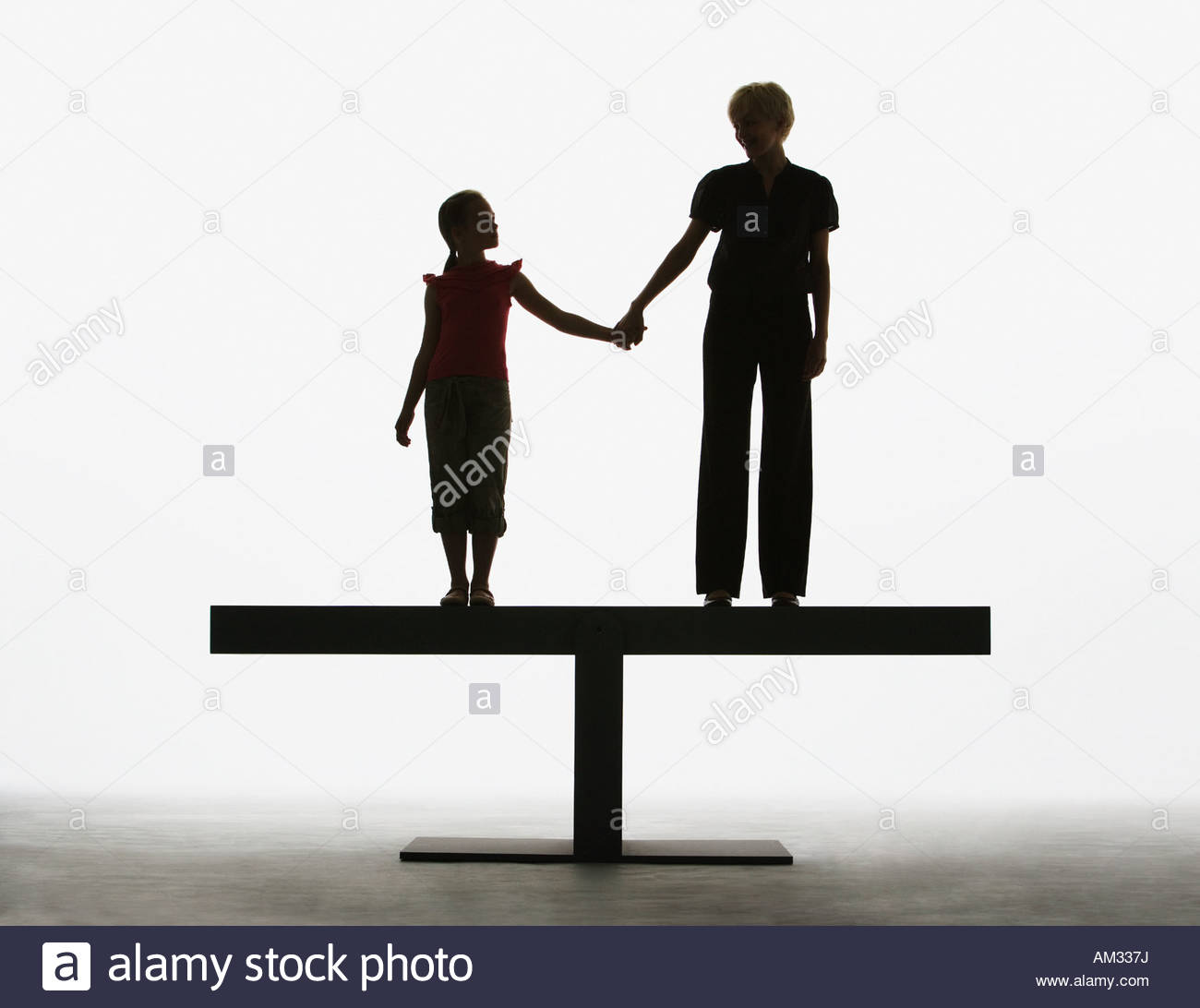 Woman and young girl holding hands on a plank Stock Photo