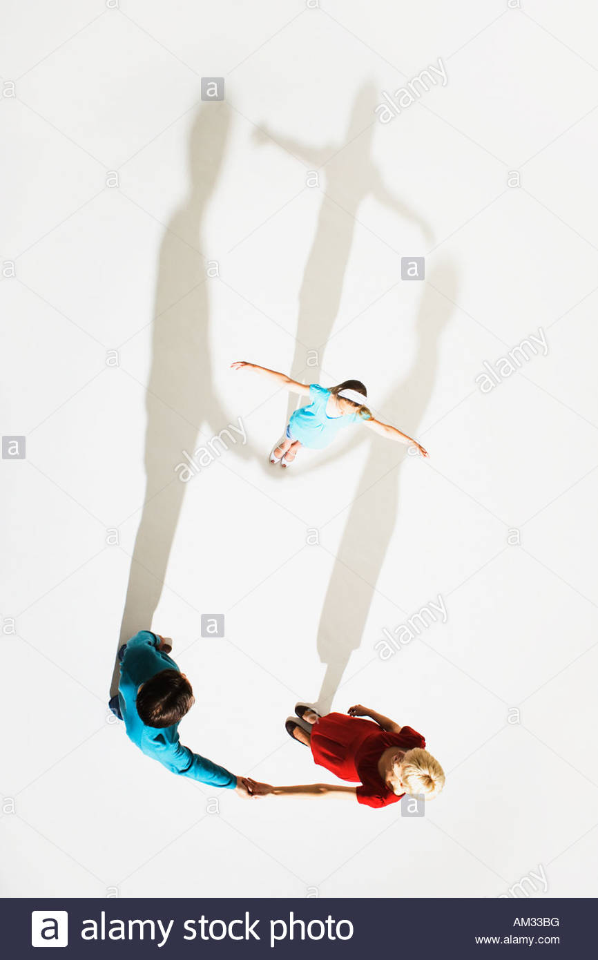 Couple and young girl standing so shadows look like they're holding her up high - Stock Image