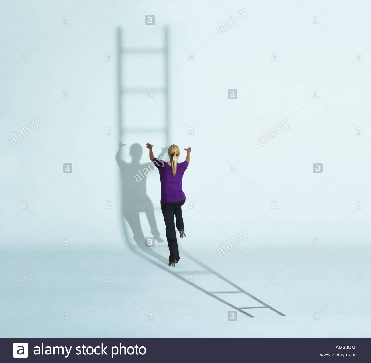 Woman climbing a ladder's shadow - Stock Image
