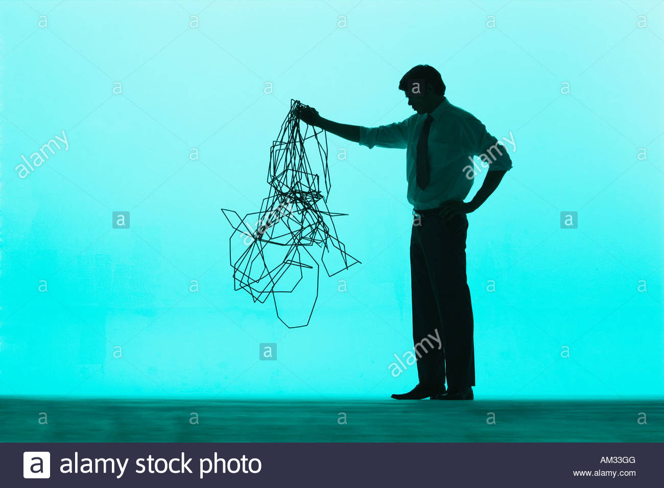 Businessman holding up a pile of cable - Stock Image