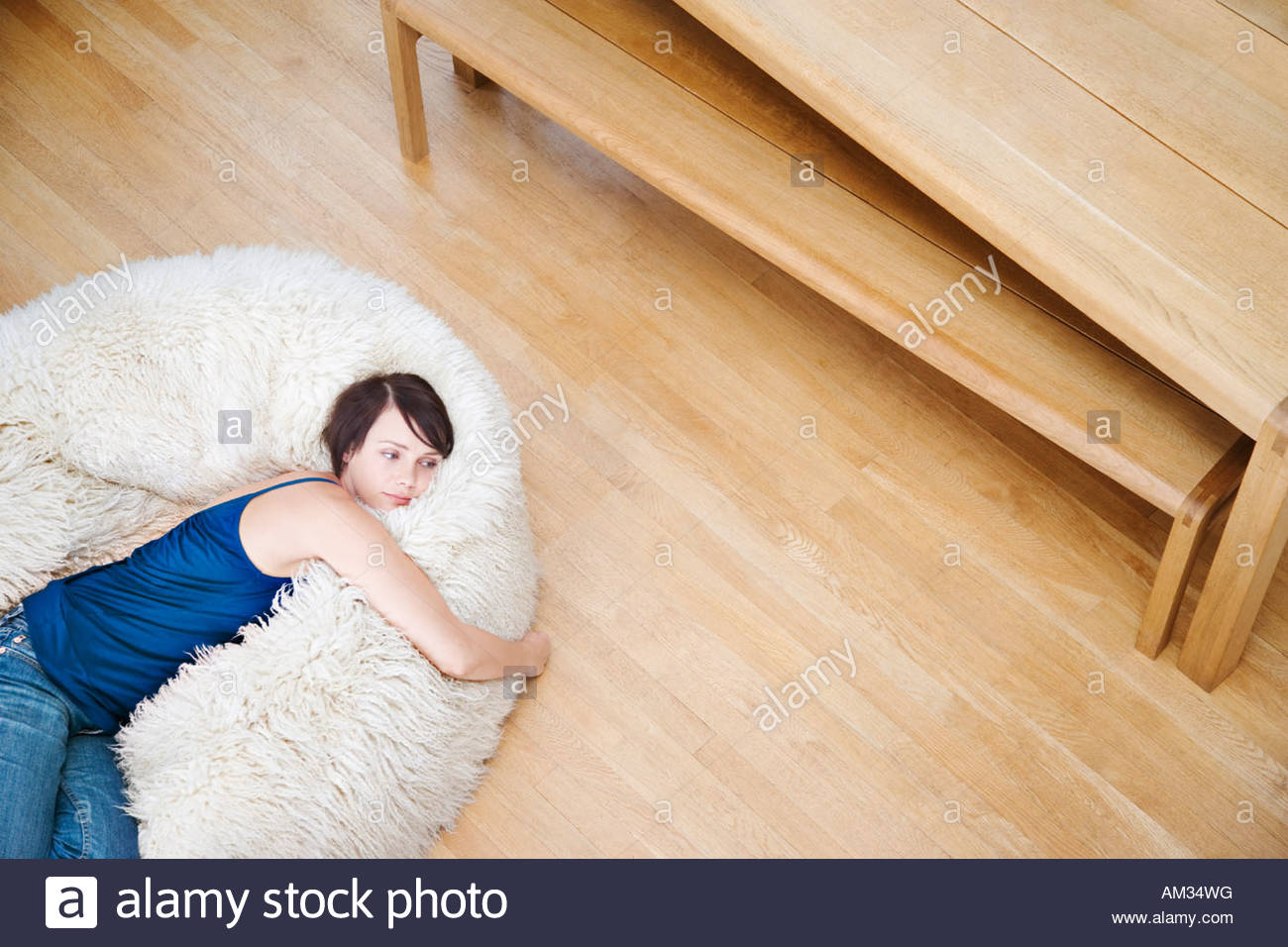 Woman on a furry bean bag chair - Stock Image