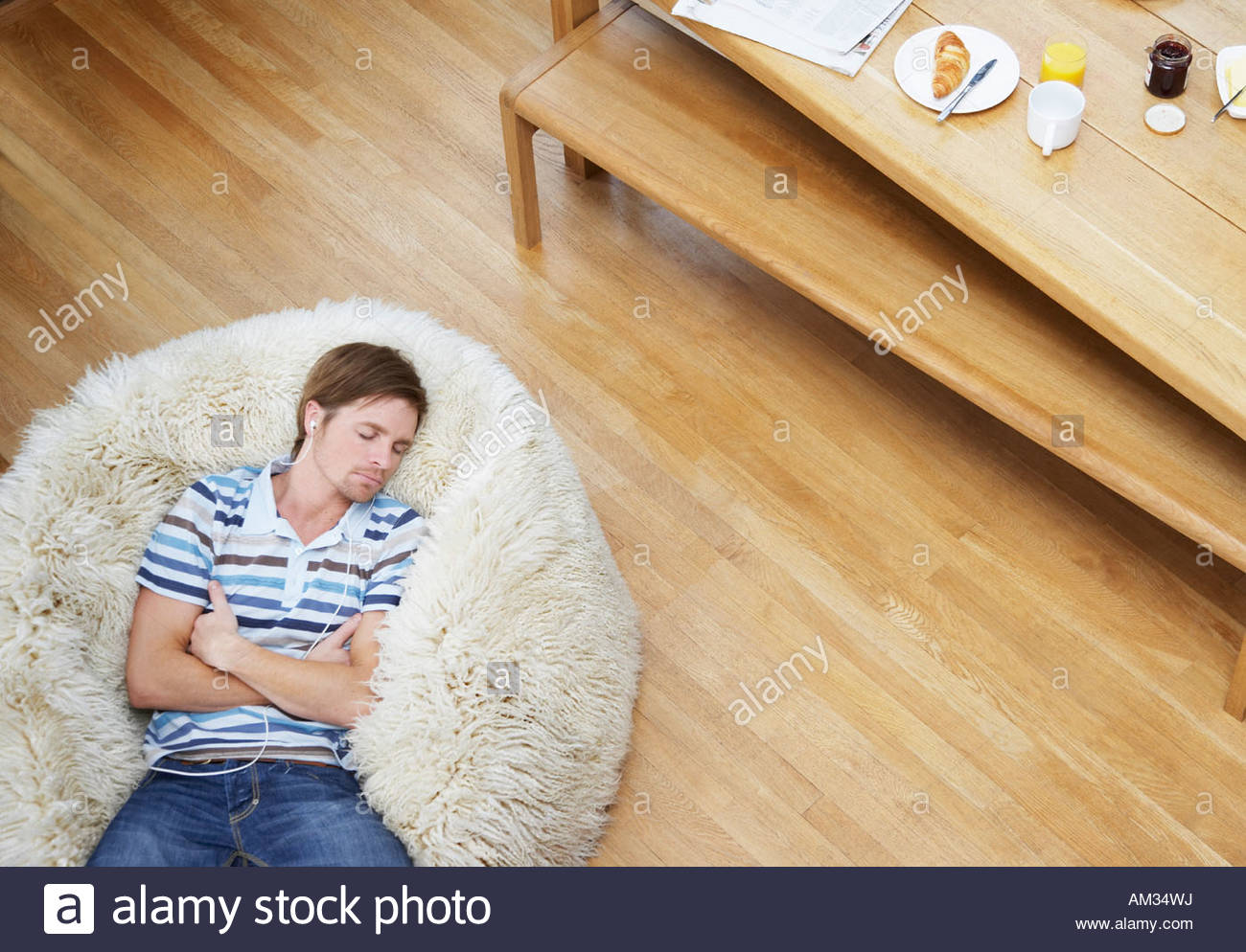 Man on a furry bean bag chair wearing earbuds - Stock Image