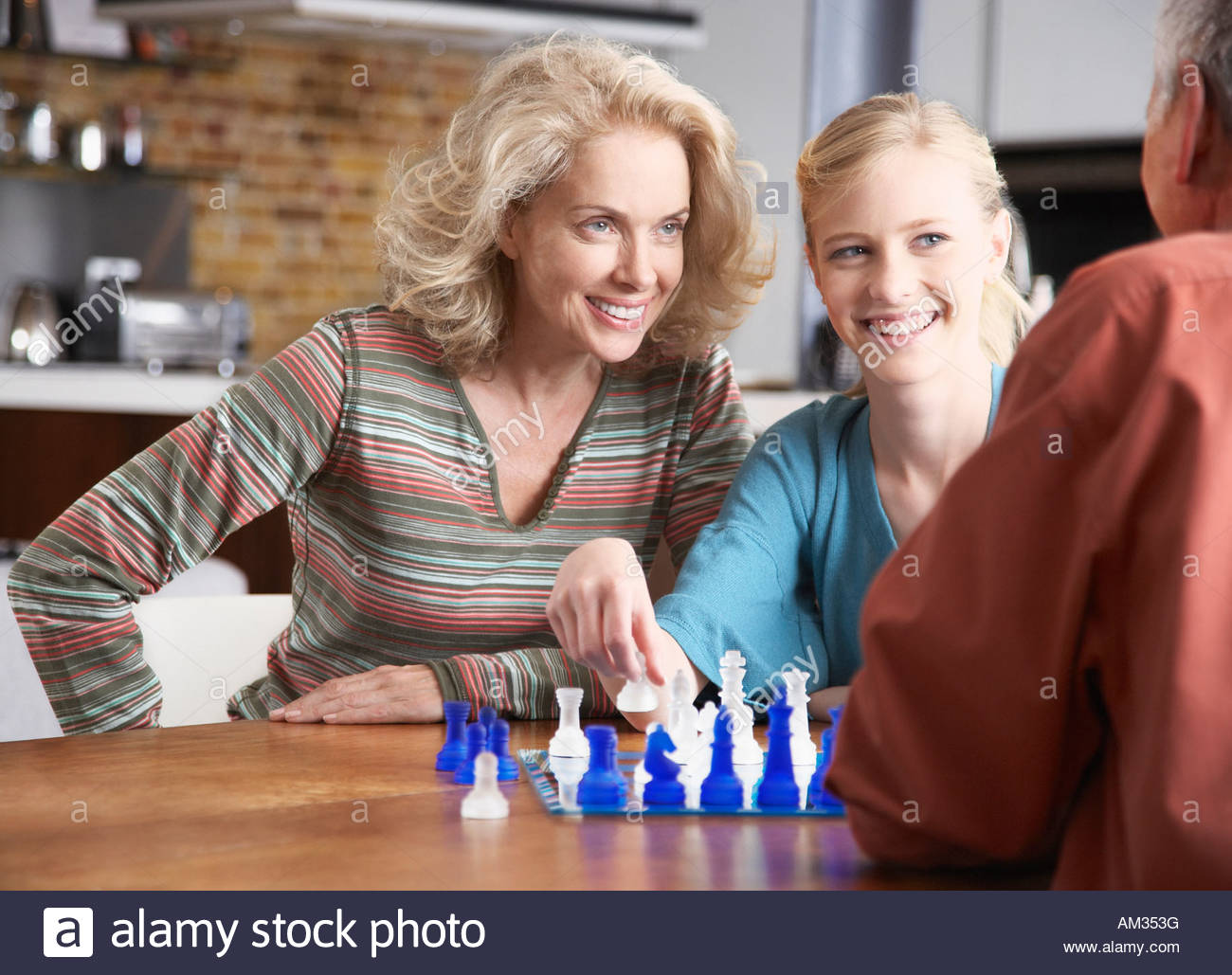 Couple playing chess with girl - Stock Image