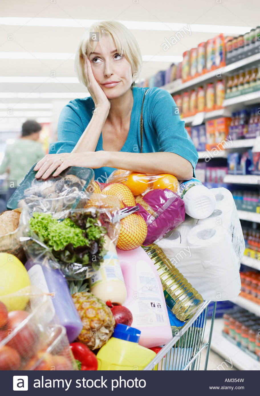Woman with shopping trolley full of groceries - Stock Image