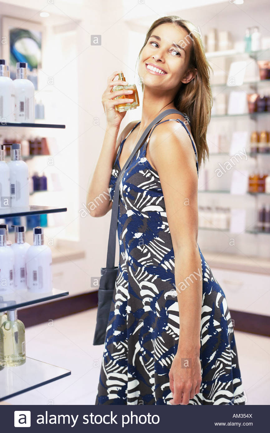 Woman spraying perfume on herself in store - Stock Image