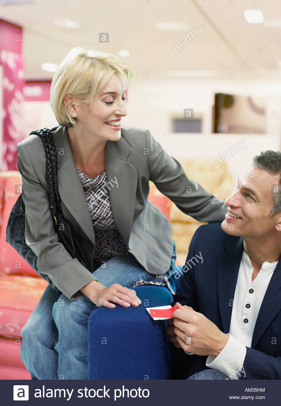Couple looking at couches in store - Stock Image