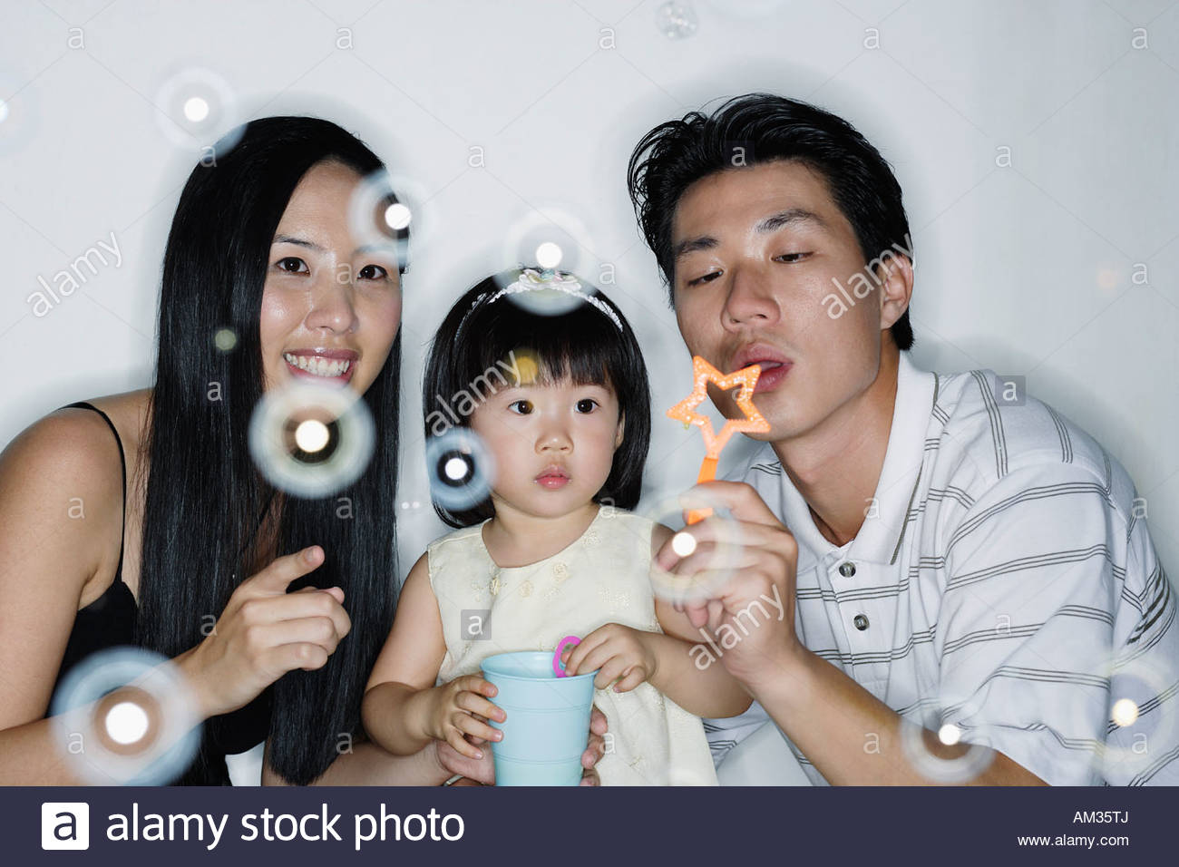 Couple with young girl blowing bubbles Stock Photo