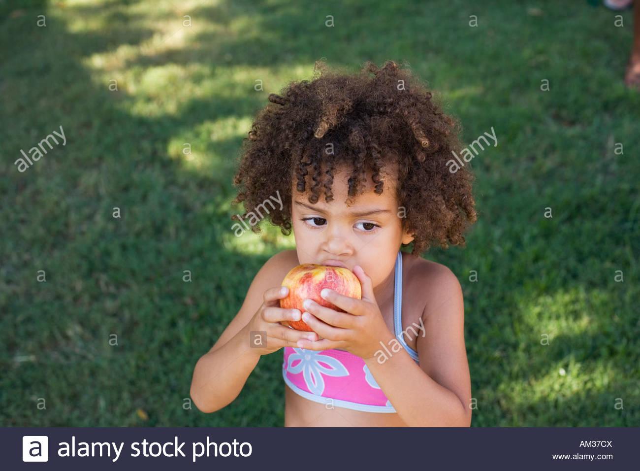 Girl in swimwear eating apple in yard - Stock Image