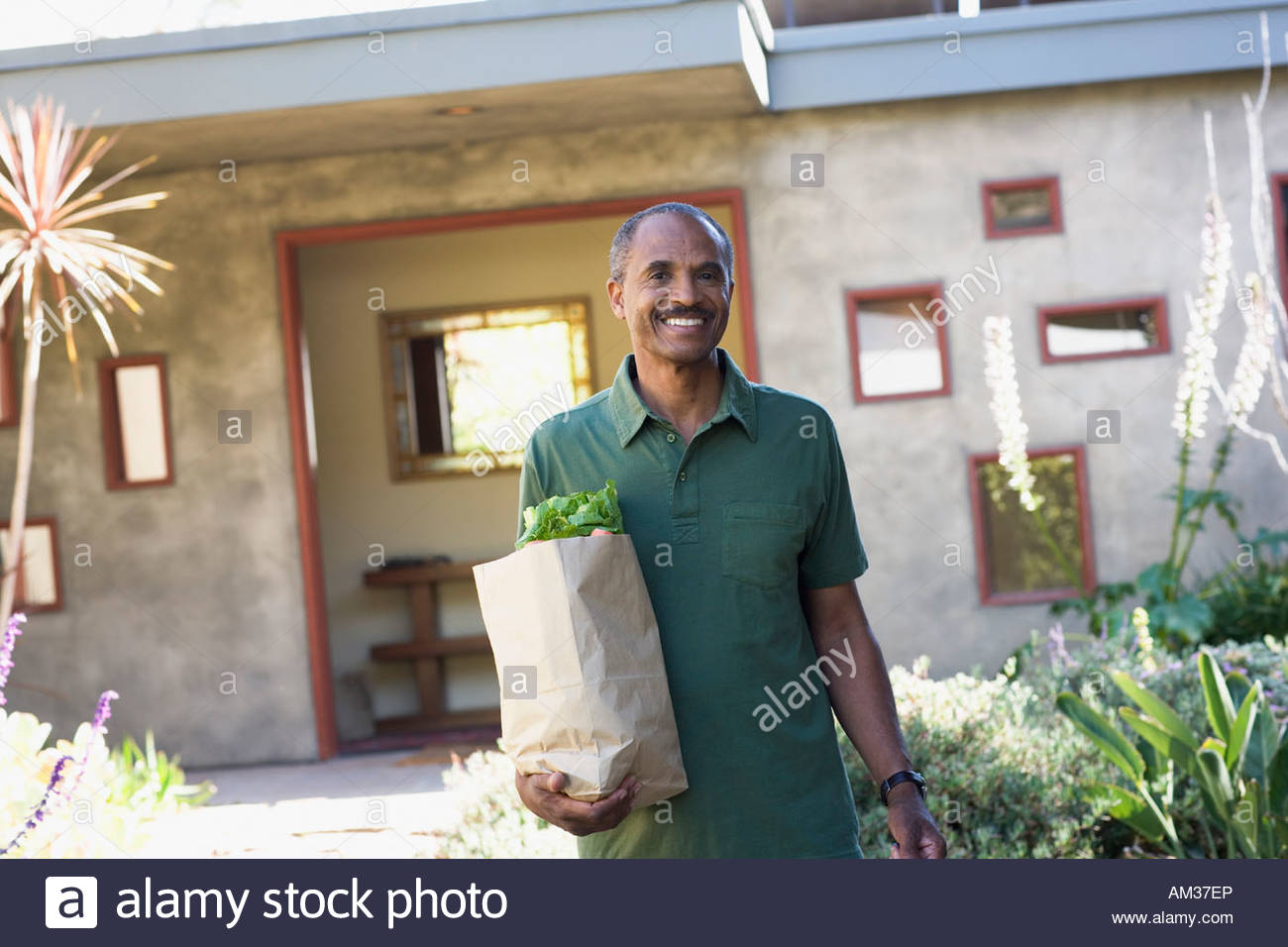 Man with brown bag of groceries outside home - Stock Image