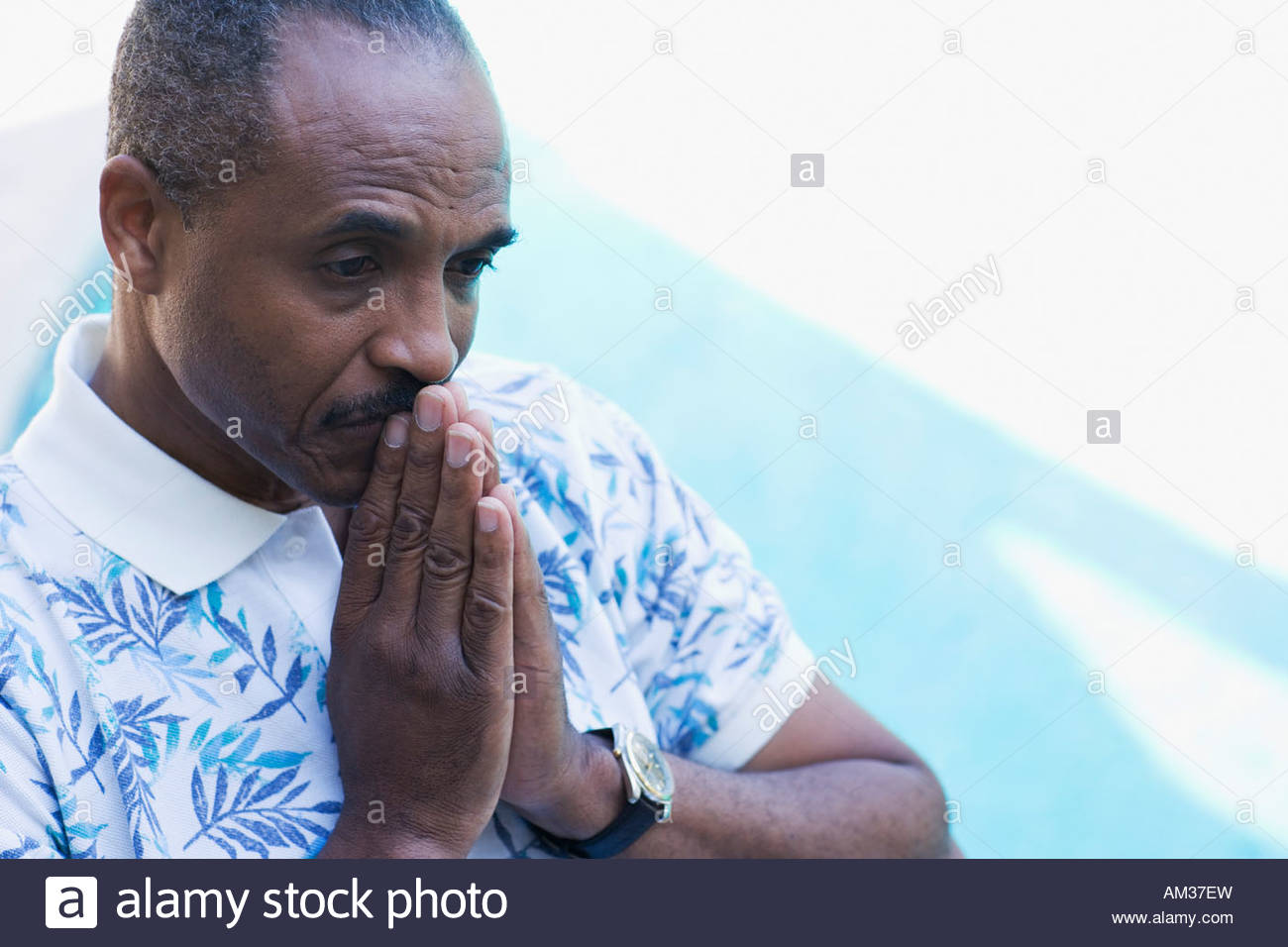 Man with hands to lips thoughtfully by pool Stock Photo