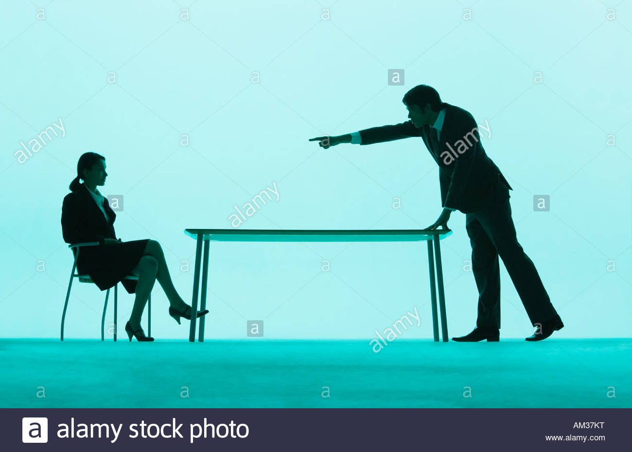 Businessman pointing at a businesswoman at a table - Stock Image