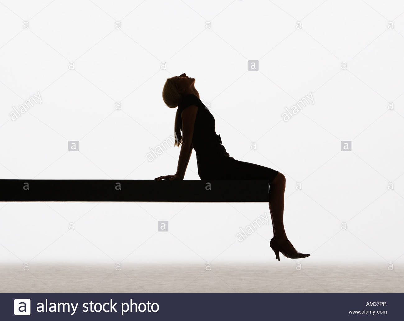 Woman sitting on edge of plank relaxing - Stock Image