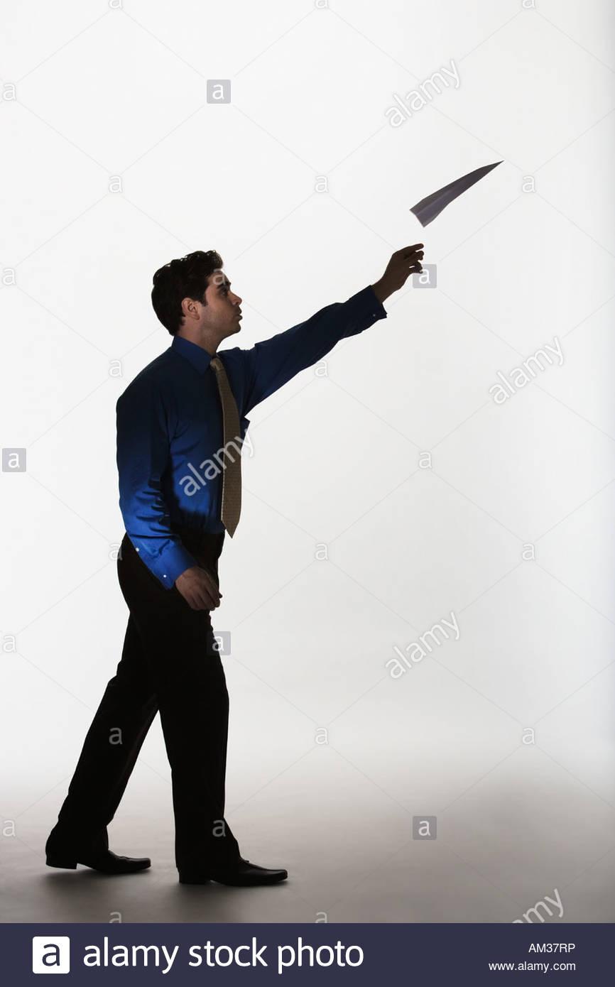 Man throwing paper airplane - Stock Image