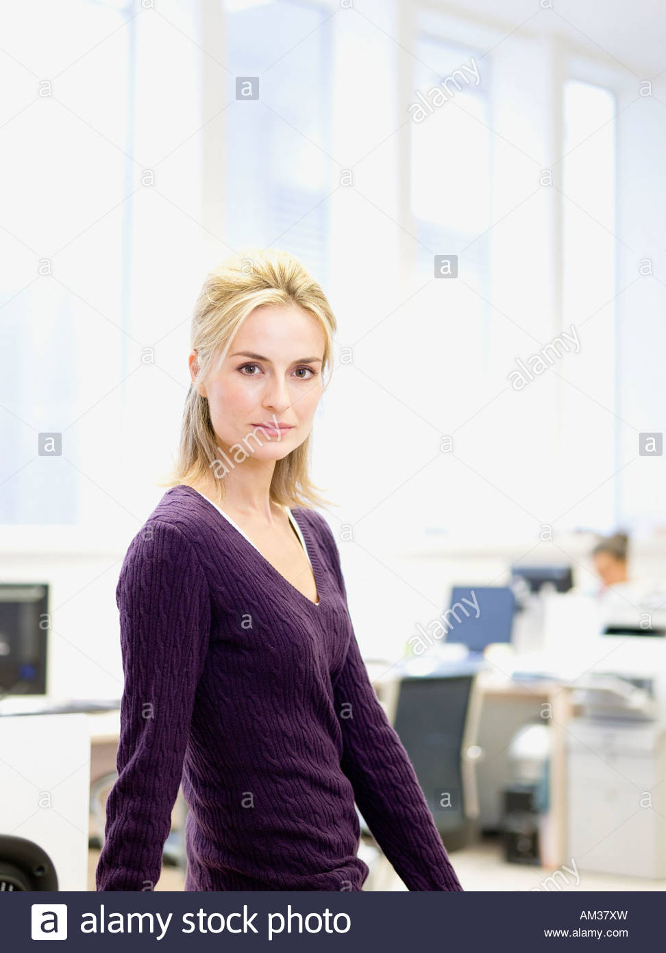 Businesswoman in office with co-worker in background - Stock Image