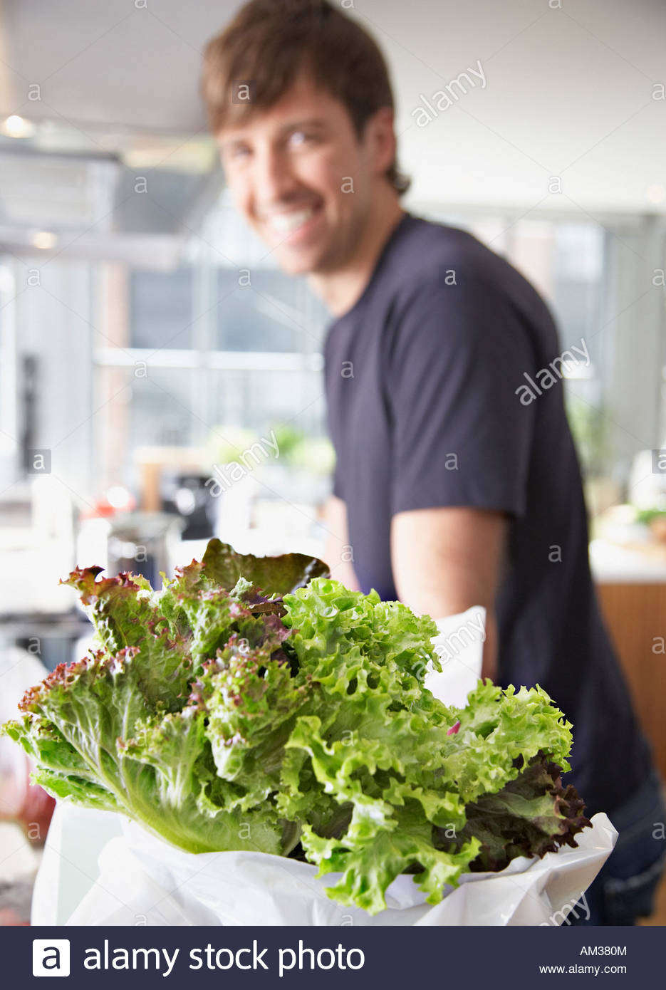 Lettuce in a bag with man in background - Stock Image