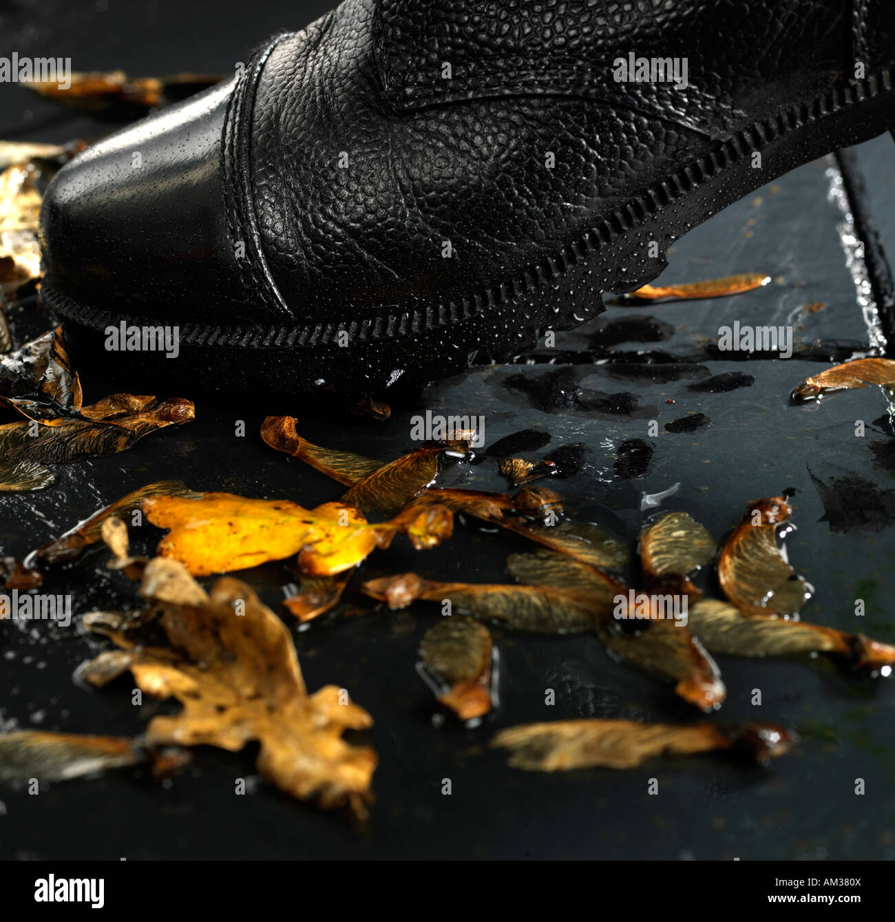 A 0455 black army boot stamping on wet autumn pavement - Stock Image