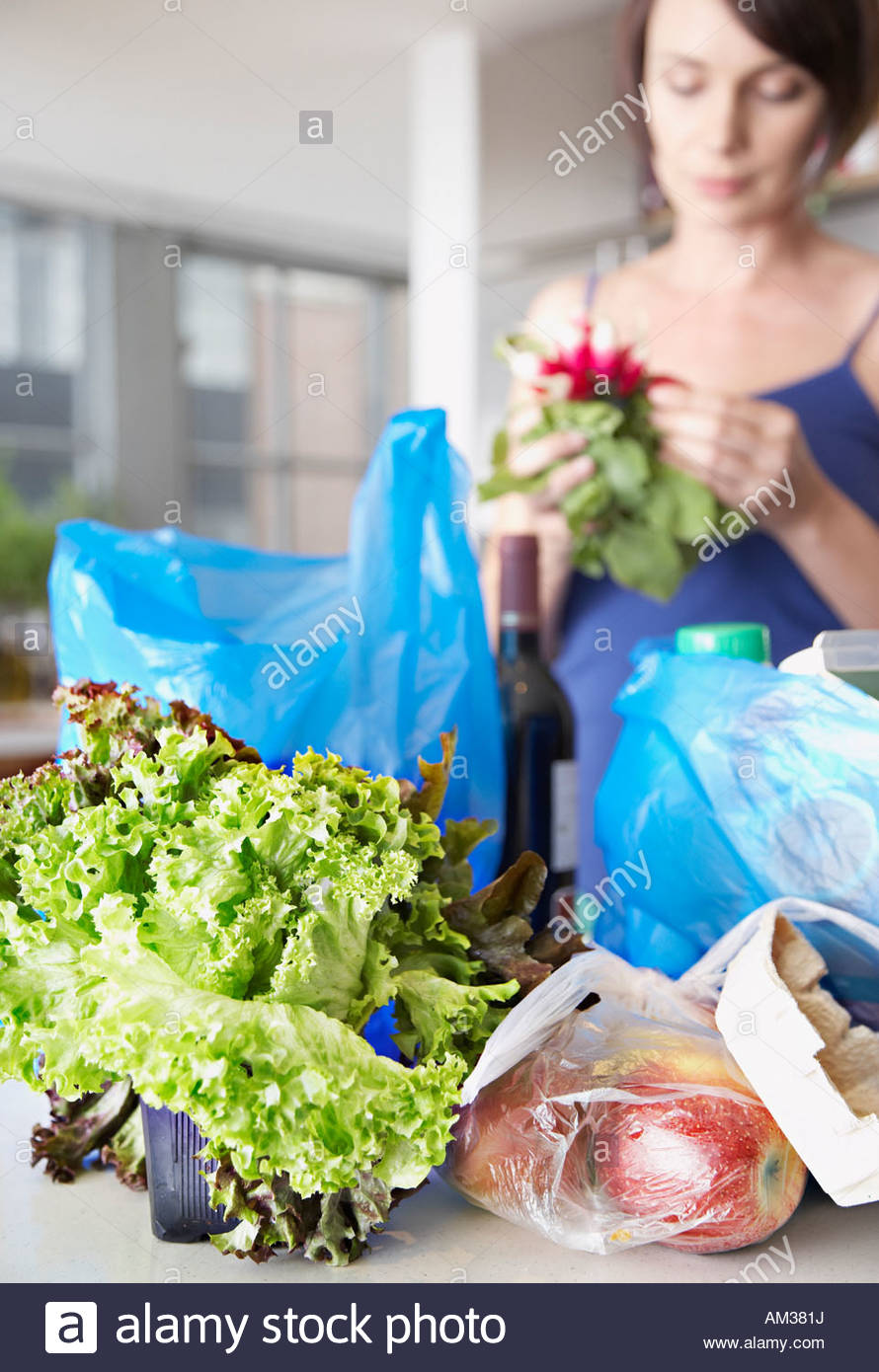 Woman with groceries and flowers in kitchen - Stock Image