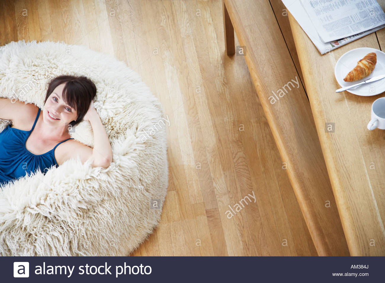Woman on furry bean bag chair in living room - Stock Image