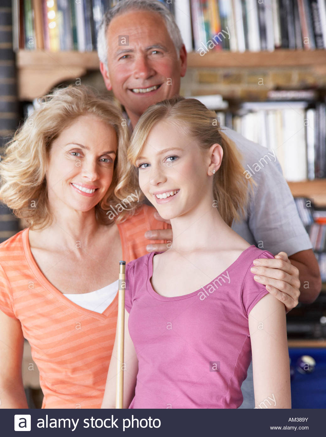 Couple with girl holding pool cues - Stock Image
