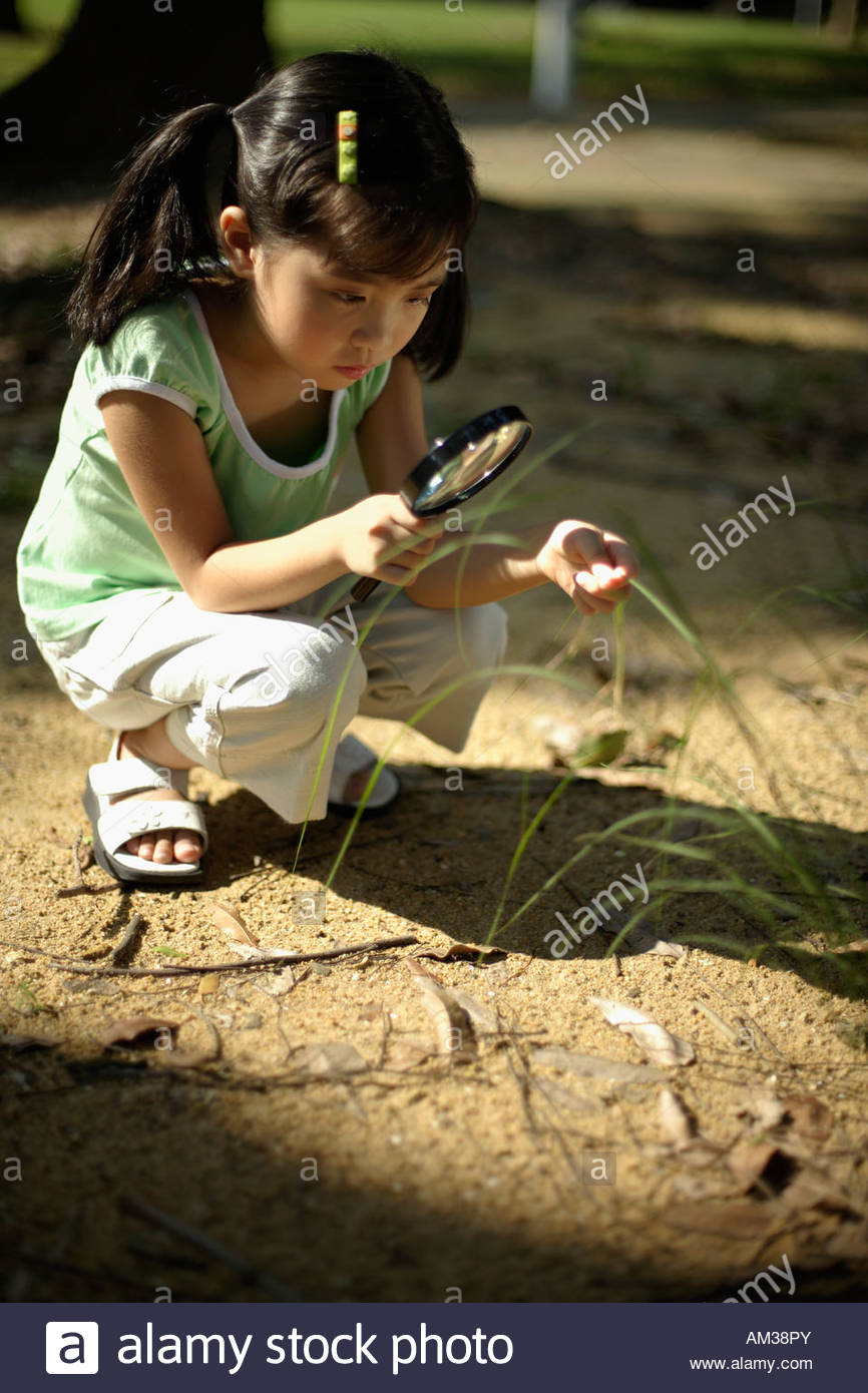 Girl with magnifying glass outdoors - Stock Image