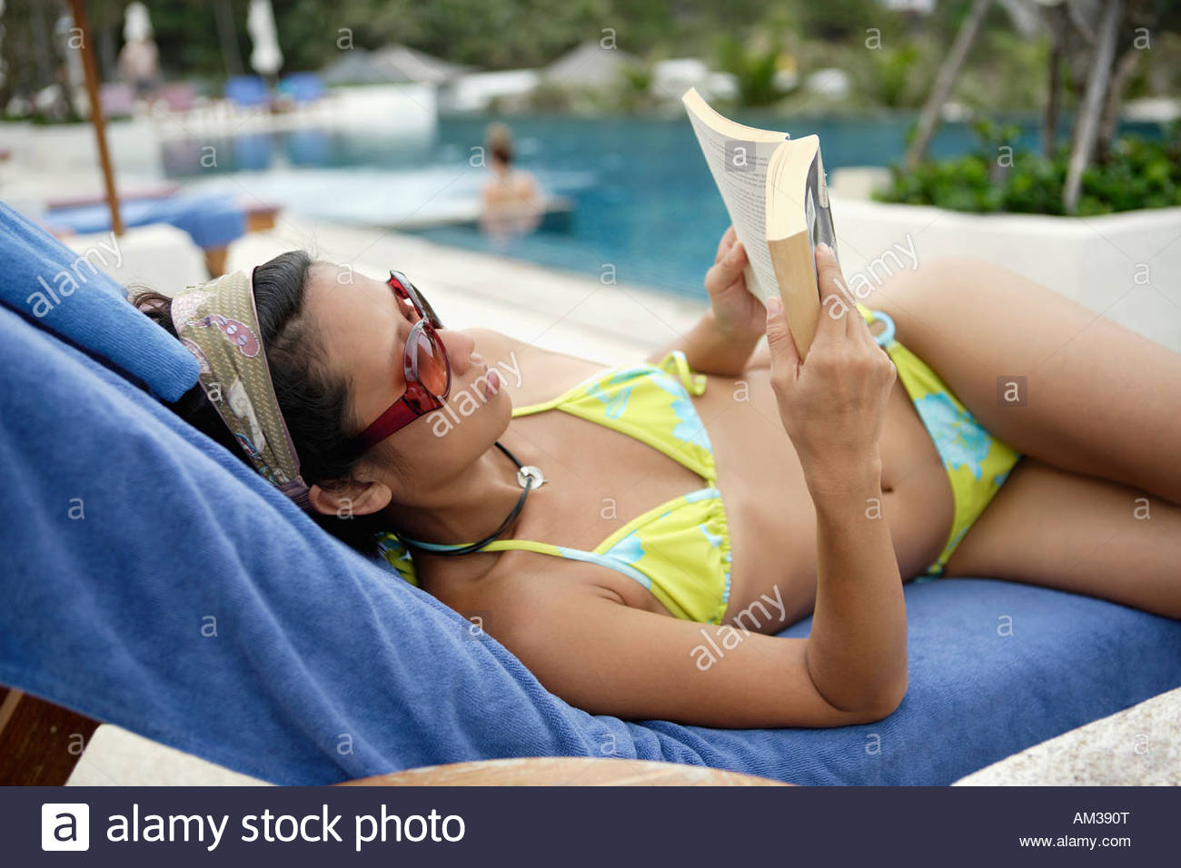 Woman lying by pool with book - Stock Image
