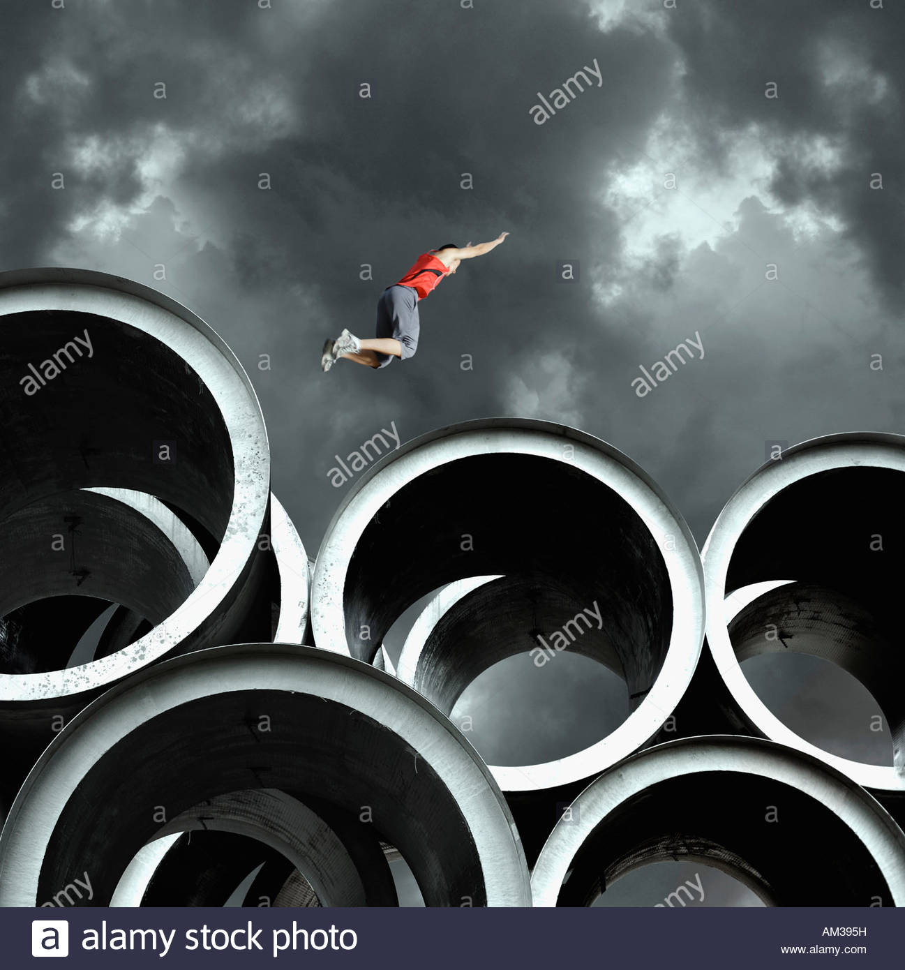 Long jumper on large cylinders Stock Photo