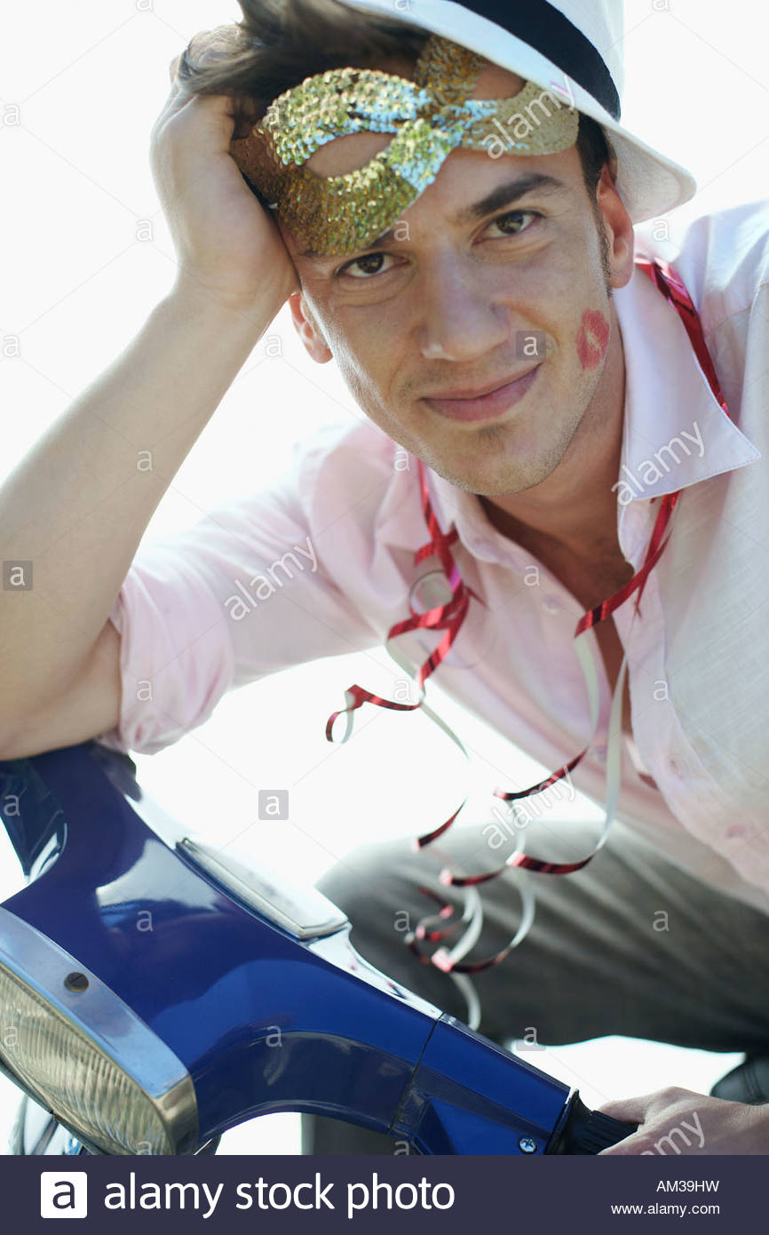 Man sitting on a scooter after a party - Stock Image