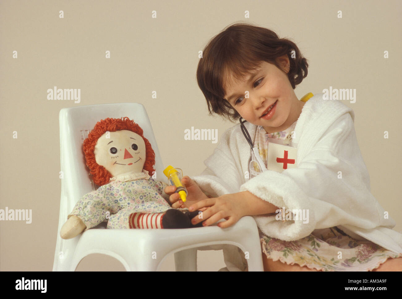 Young girl playing doctor with her doll - Stock Image