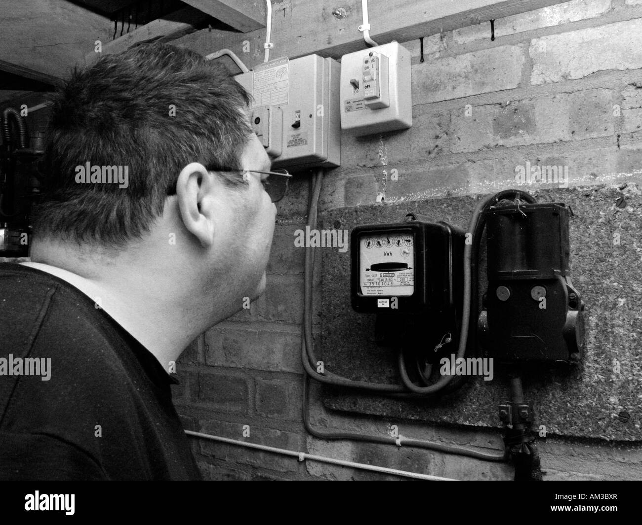 man reading and checking electric meter in garage - Stock Image