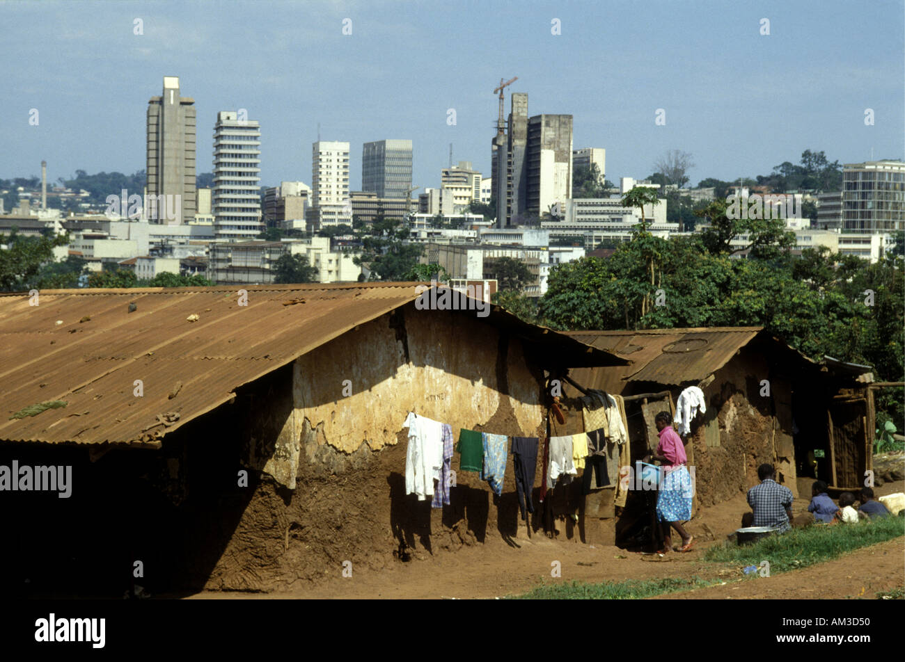 Shanty town houses within sight of the high rise modern buildings in central Kampala capital city of Uganda East Africa - Stock Image