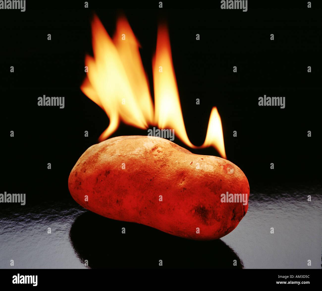 hot potato, potato on fire with flames - Stock Image