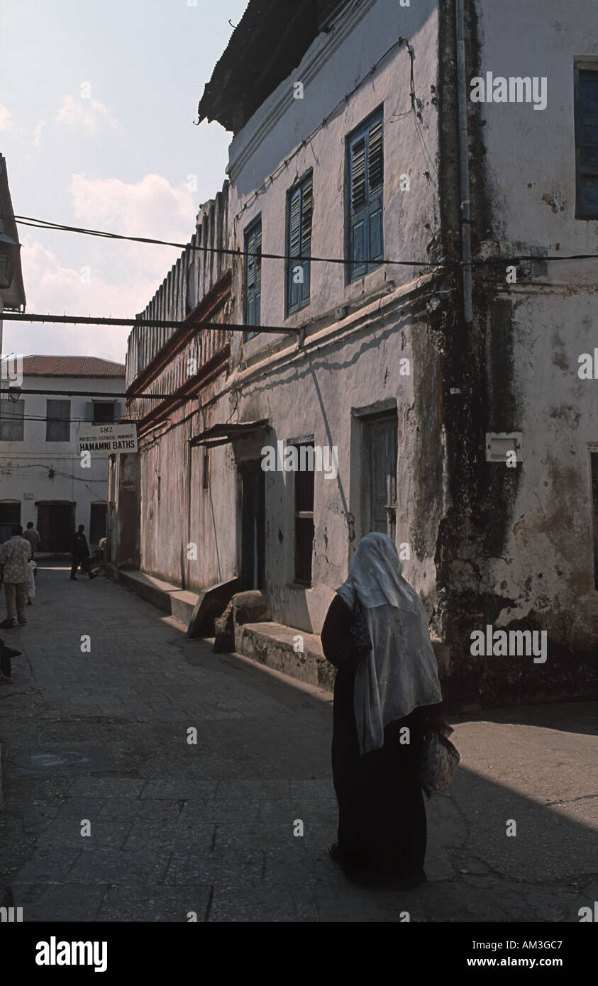 Old Stone Town is a warren of narrow streets Historic trading town Zanzibar Tanzania Woman walking near Hamamni Persian Baths - Stock Image