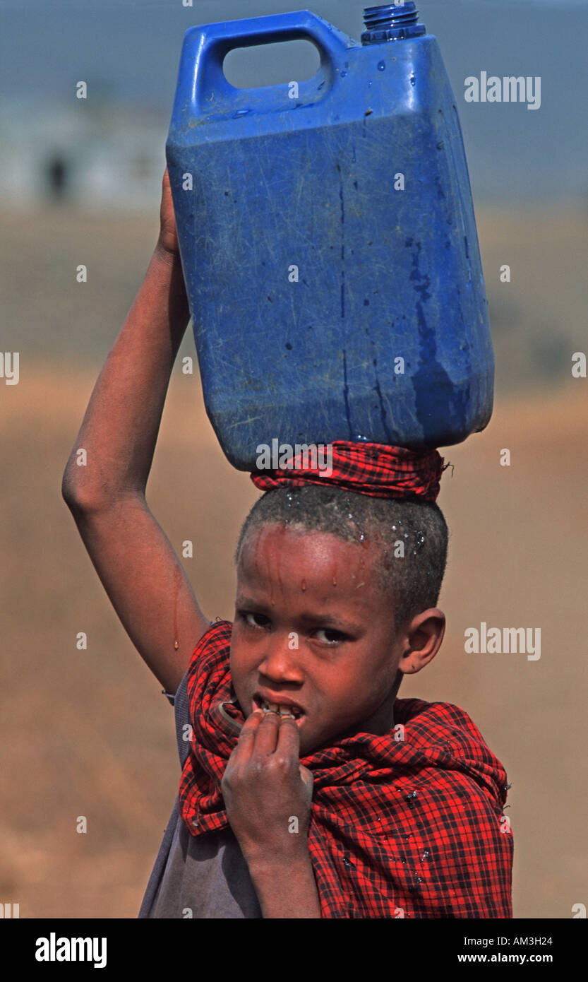 Masai child carrying water home in a plastic tank Tribal communities N of Arusha nr the weekly cattle market Tanzania E Africa - Stock Image