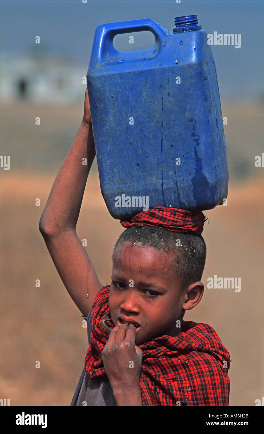 Masai child carrying water home in a plastic tank Tribal lands N of Arusha nr the weekly cattle market Tanzania E Africa - Stock Image