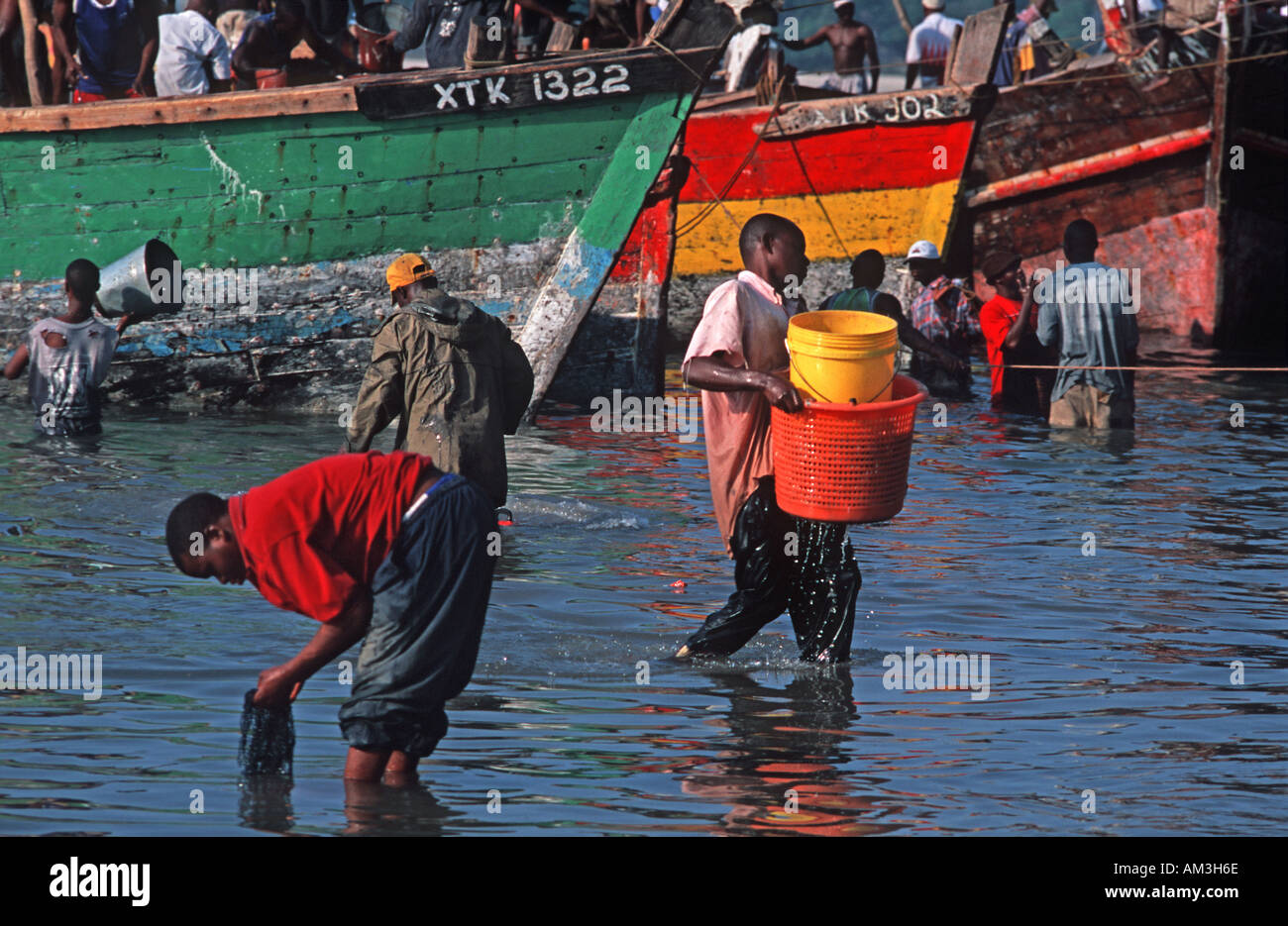 Boats moored beside the fish market Transferring fish from boat to shore Dar es Salaam Tanzania East Africa - Stock Image