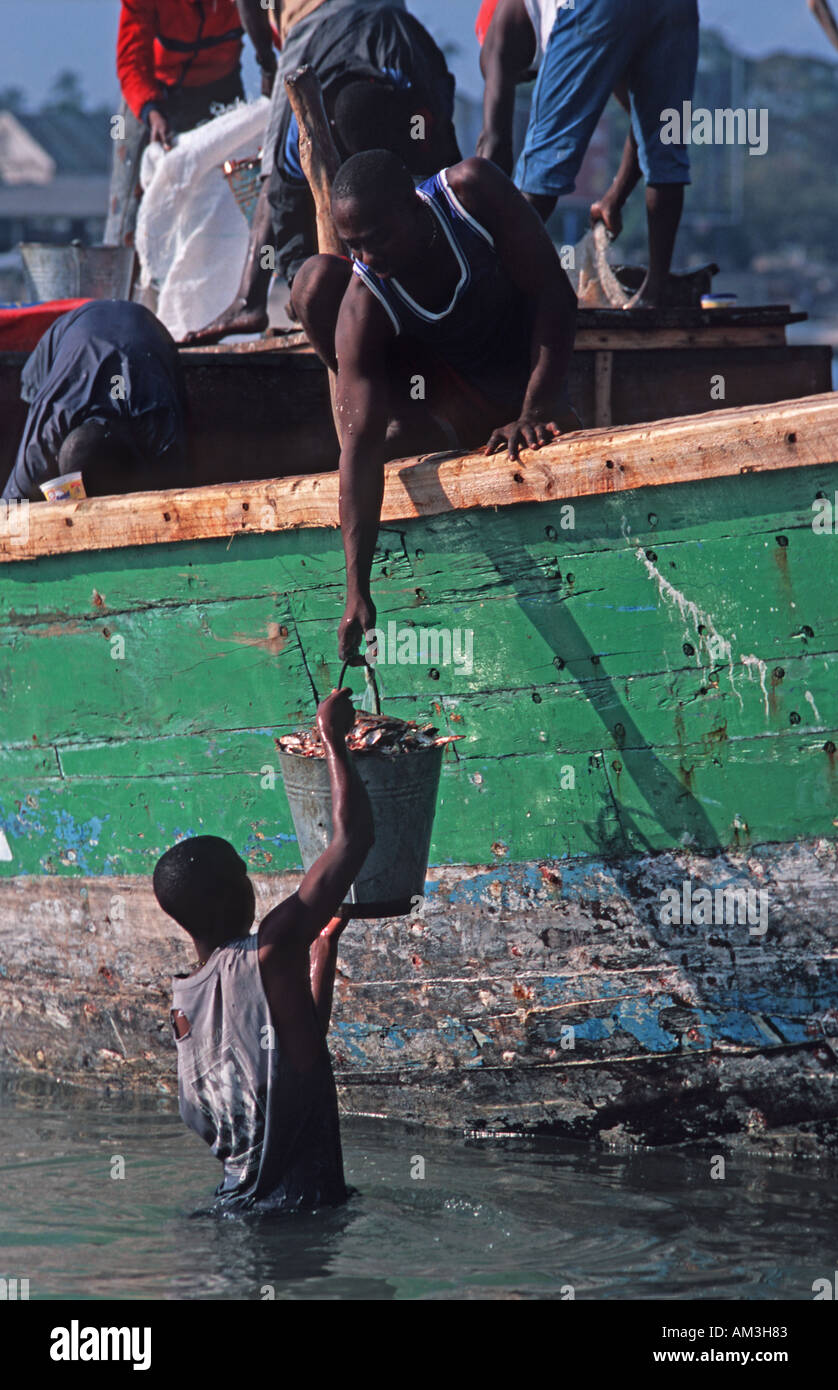 Boat moored beside the fish market passing fish from boat to bucket to shore Dar es Salaam Tanzania East Africa - Stock Image