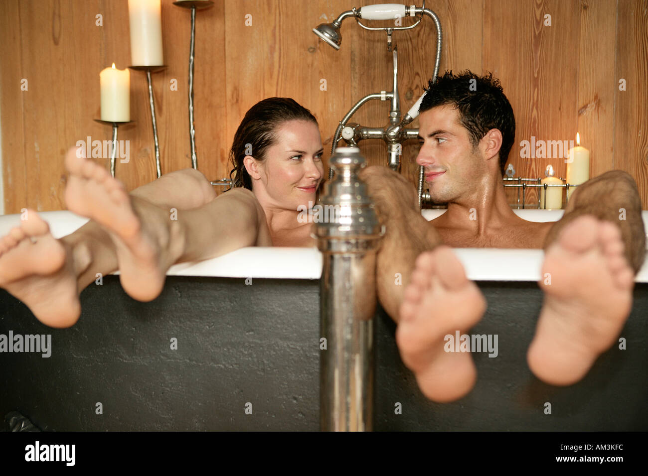 Couple in roll top bath smiling at each other - Stock Image