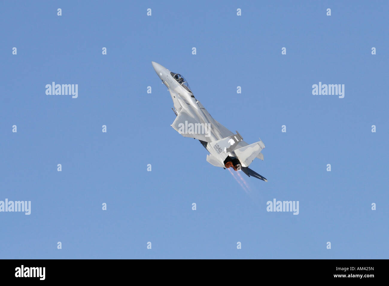 F16 in a steep climb against a blue sky Stock Photo