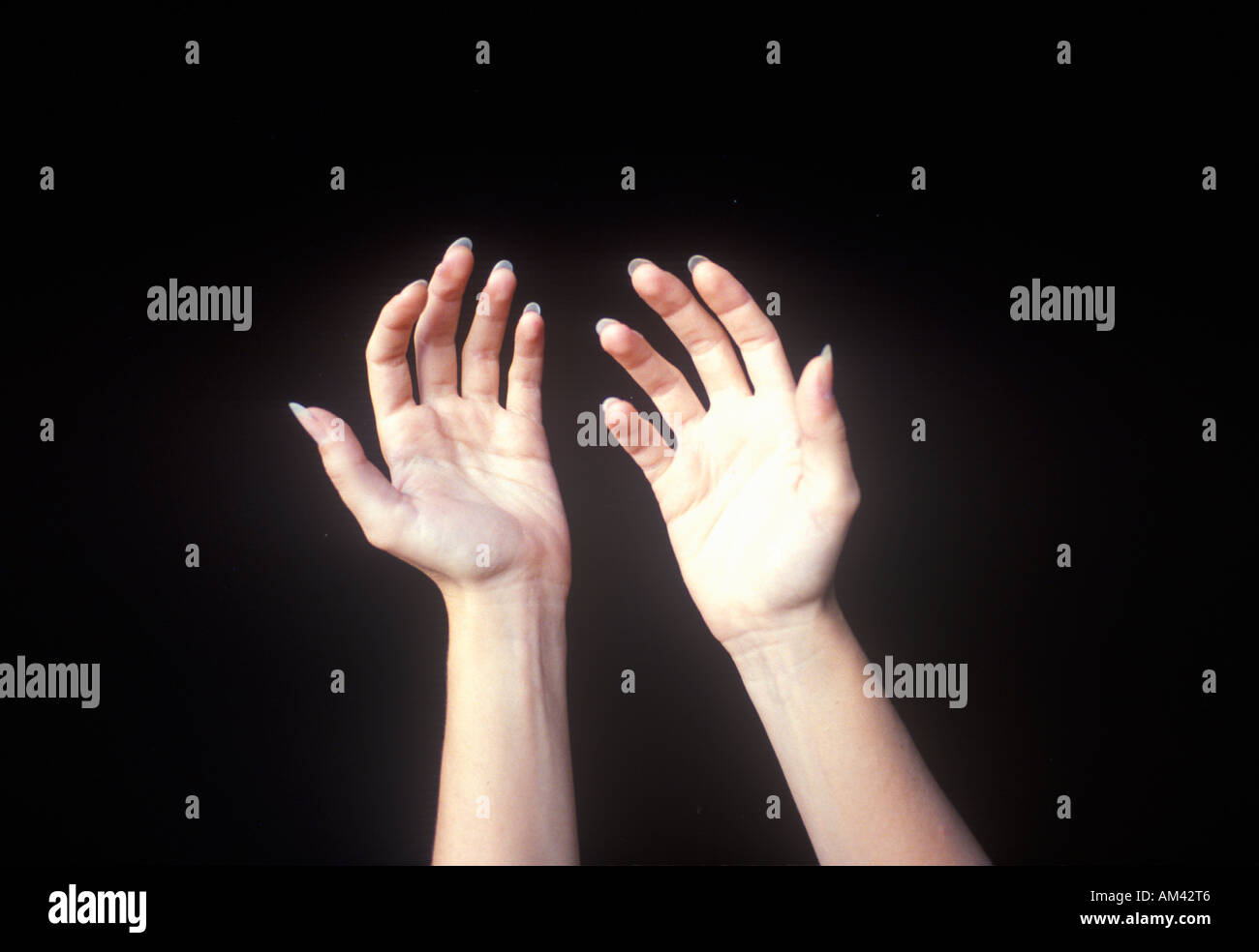 Special effects composite of two hands and black sky - Stock Image