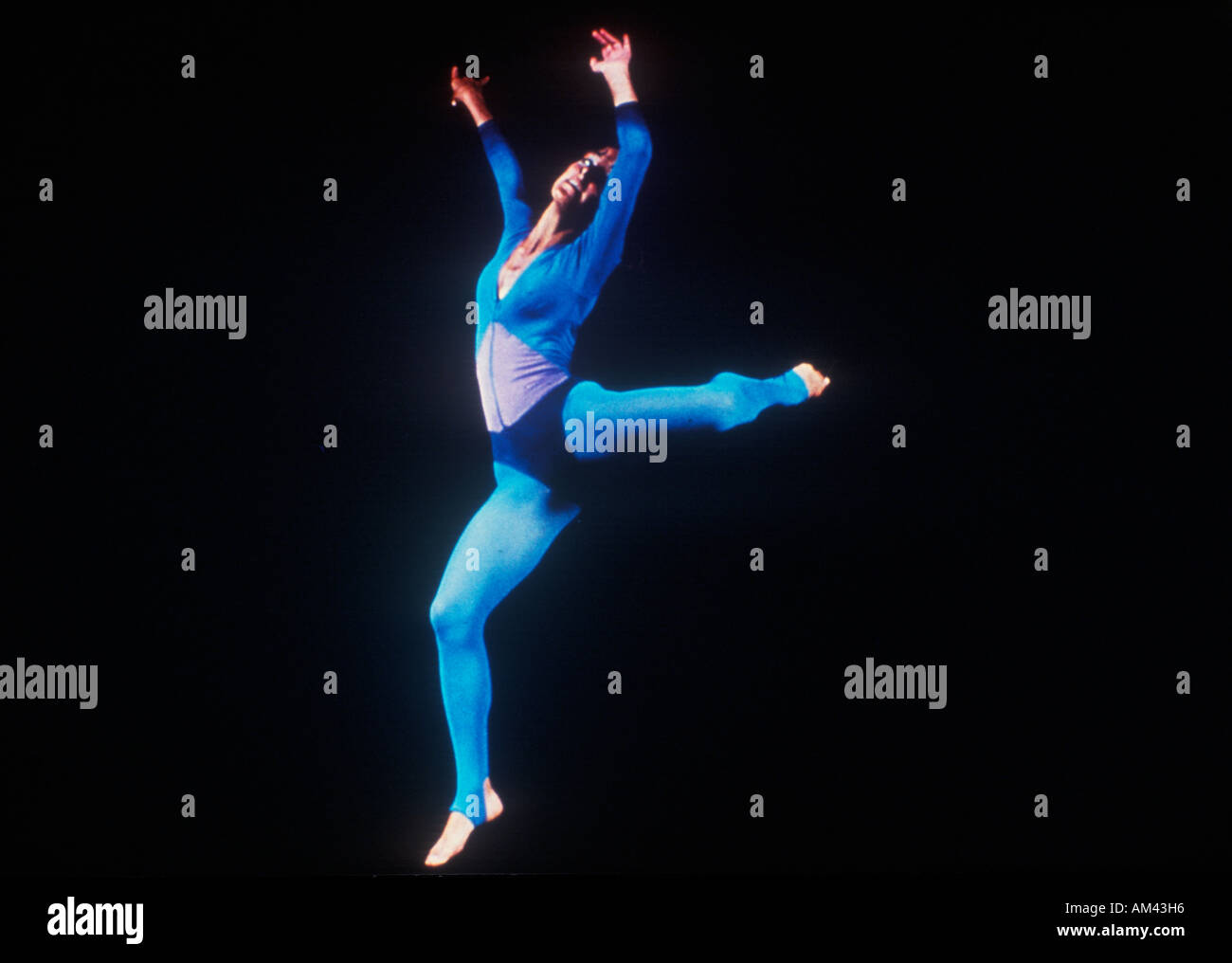 A dancer stretching on a darkened stage - Stock Image