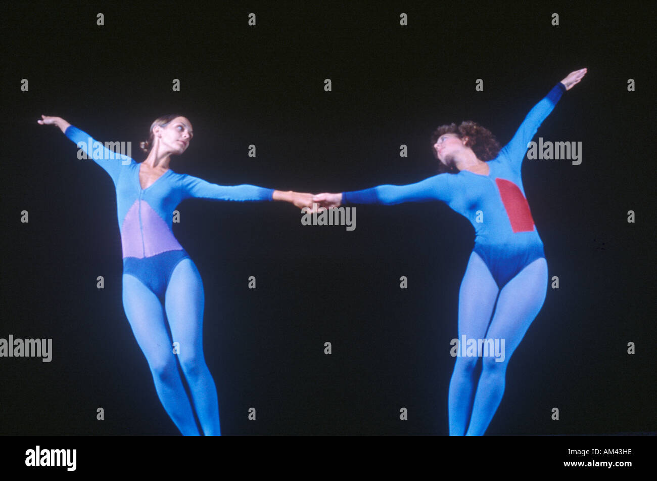 Two dancers stretching on a darkened stage - Stock Image