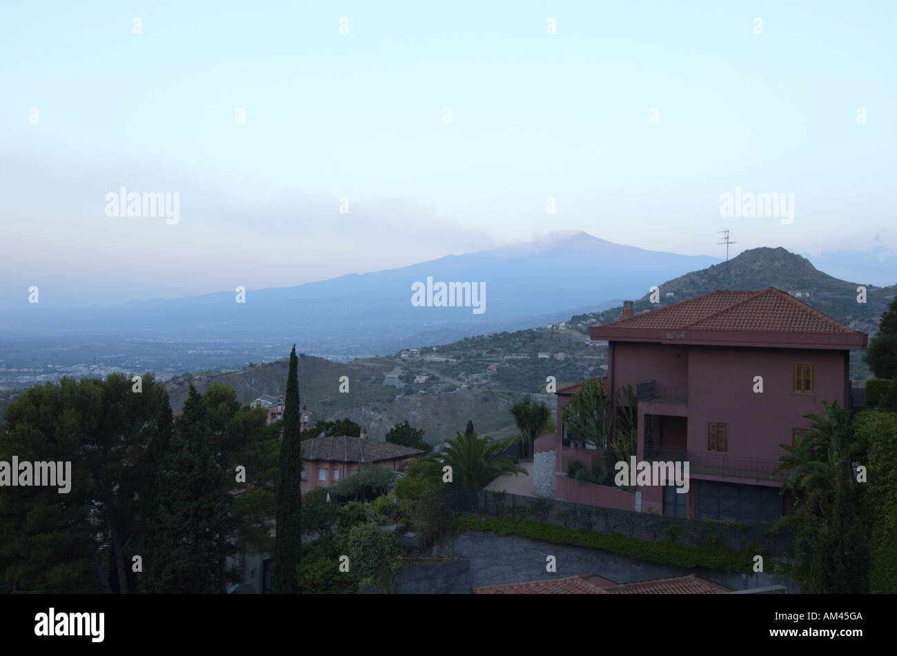 Mt Etna emitting steam and smoke as seen from Taormina at sun rise Sicily Italy July 2006 Stock Photo